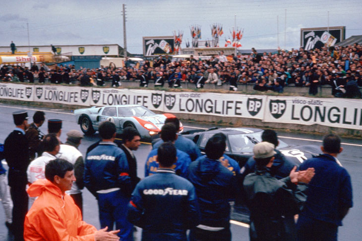 24 Hours of LeMans, LeMans, France, 1966. Chris Amon/Bruce McLaren and Ken Miles/Denis Hume pass the Ford pits on the way to the finish line. CD#0554-3252-2890-18.